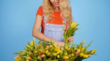 Young female florist with big box of yellow tulips