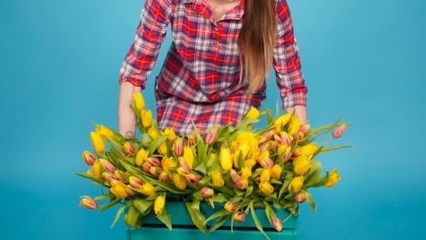 Mladé samice květinářství s velkou krabici žlutých tulipánů