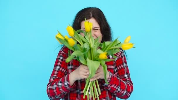 Young woman with tulips on blue background