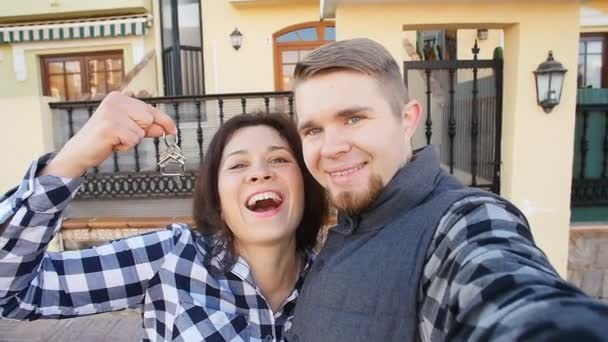 Young Couple with keys standing outside new home and taking a selfie