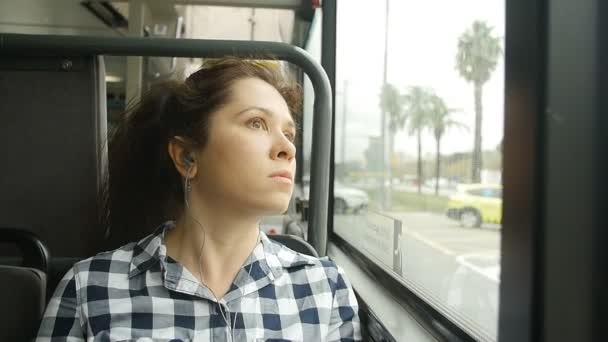 Young woman looking out the window of the bus