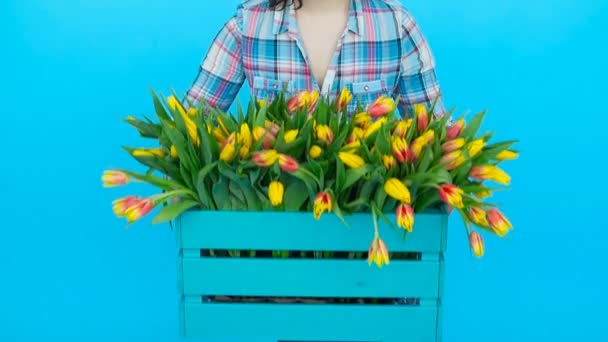 Pretty Young female florist with box of tulips