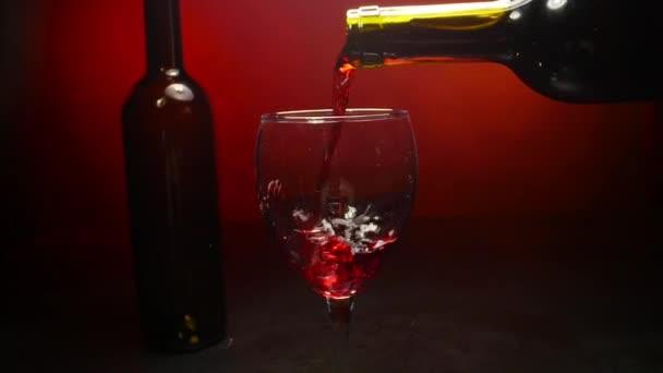 Červené víno nalévání do sklenice vína na červeném pozadí ve zpomaleném filmu