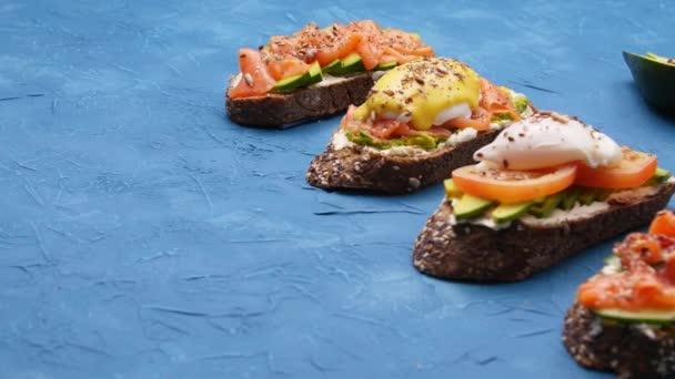 Egészséges étel koncepció. Nyitott szendvicsek avokádóval a kék asztalon