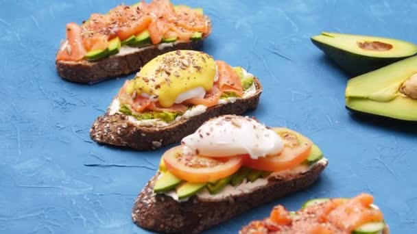 Healthy food concept. Open sandwiches with avocado on a blue table