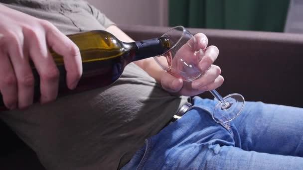 Muž na gauči nalévá víno