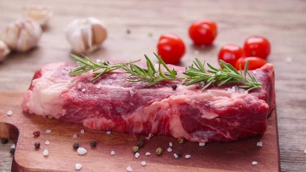 rohes Frischfleisch-Steak mit Kräutern und Gewürzen auf rustikalem Hintergrund
