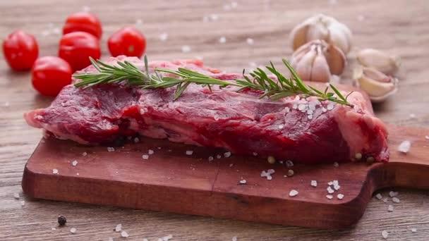 Koncept vaření. Syrový hovězí steak na dřevěném stole.