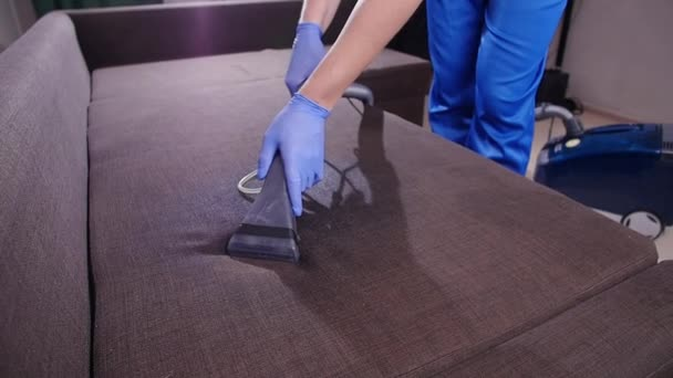 Sauberkeitskonzept. Reinigungskraft entfernt Schmutz von Polstermöbeln