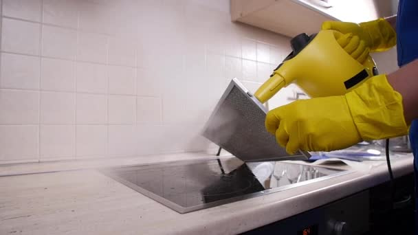 Koncept úklidu domu. Muž úklid kuchyně s parní čistič