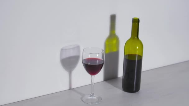Conceptual shot, a bottle of wine and a glass on a white background