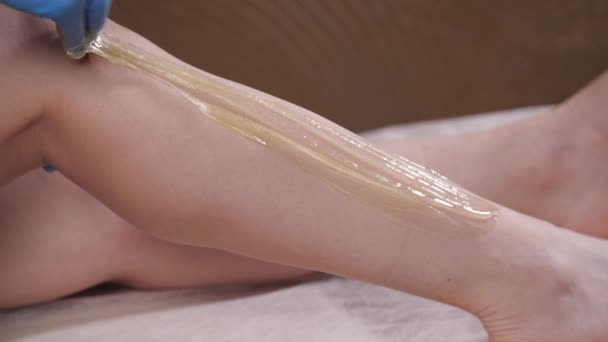 Beauty and body care concept. Sugaring epilation skin care with liquid sugar at legs
