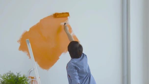Wohnungssanierungskonzept. Glückliche Frau mittleren Alters bemalt weiße Wand mit Farbroller, orange Farbe