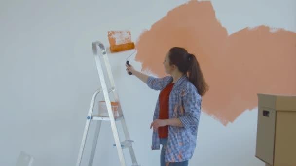 Singleton Lifestylekonzept. Junge glückliche Frau bemalt ihre Wände mit einem Roller orange