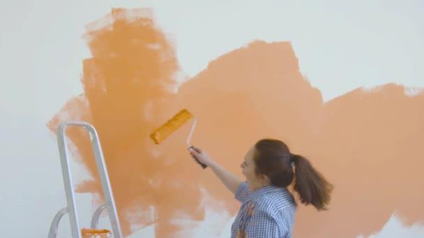 Singleton Lifestyle- und Renovierungskonzept. Junge lächelnde Frau mit Malerrolle bemalt die Wand in der Wohnung und tanzt