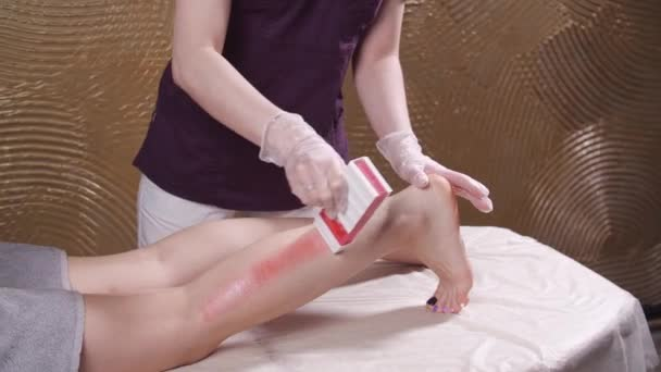Beauty and body care concept. Beautician doing wax depilation. Spa studio