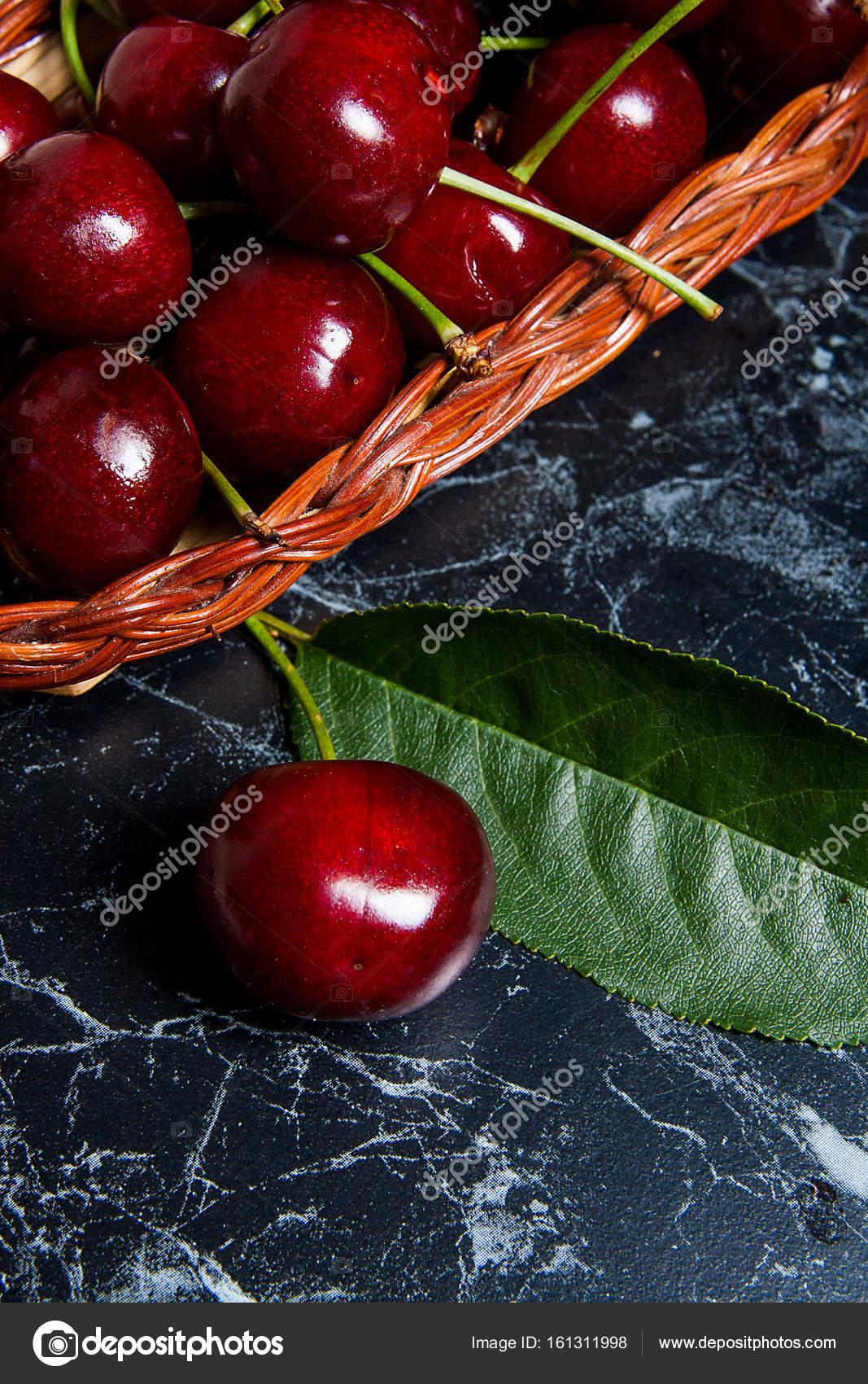 Mehrere rote Süßkirschen und großen grünen Blatt auf den Tisch. Fres ...