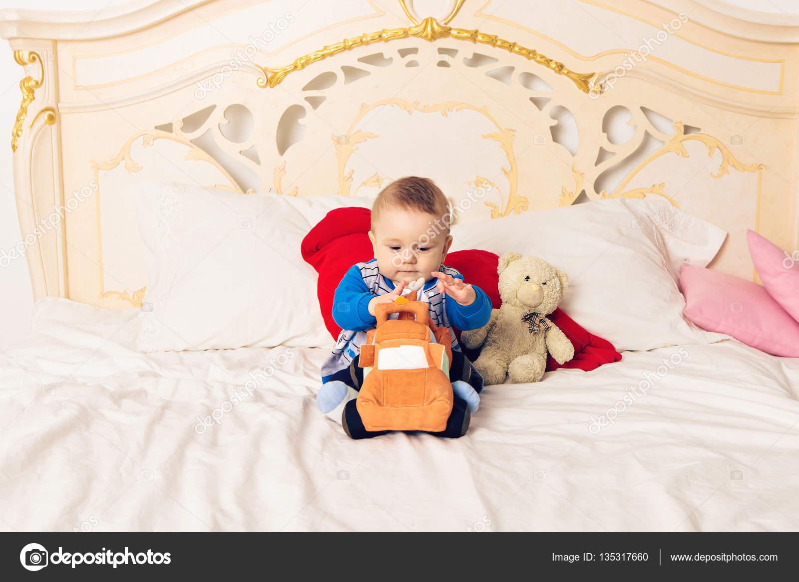 Bett Kleinkind Junge ~ Niedlichen kleinkind junge sitzt auf dem bett und spielt mit