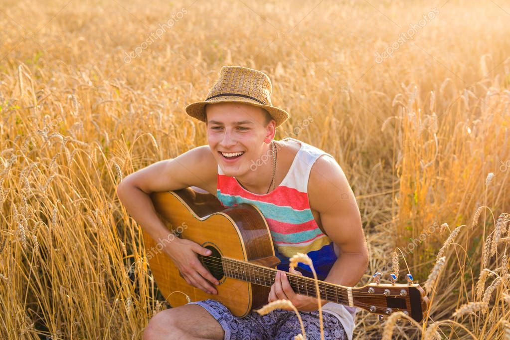 A man is playing guitar in the field at relax day with sun light.