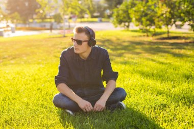 Portrait of a relaxed young man sitting on grass in park and listening to music on headphones.