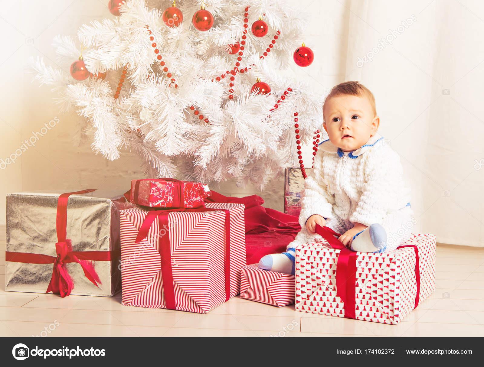 fd096057a62 Μωρό 1 έτους κάθεται σε συσκευασία δώρου με Χριστουγεννιάτικο δέντρο. Καλά  Χριστούγεννα. Περίοδος διακοπών