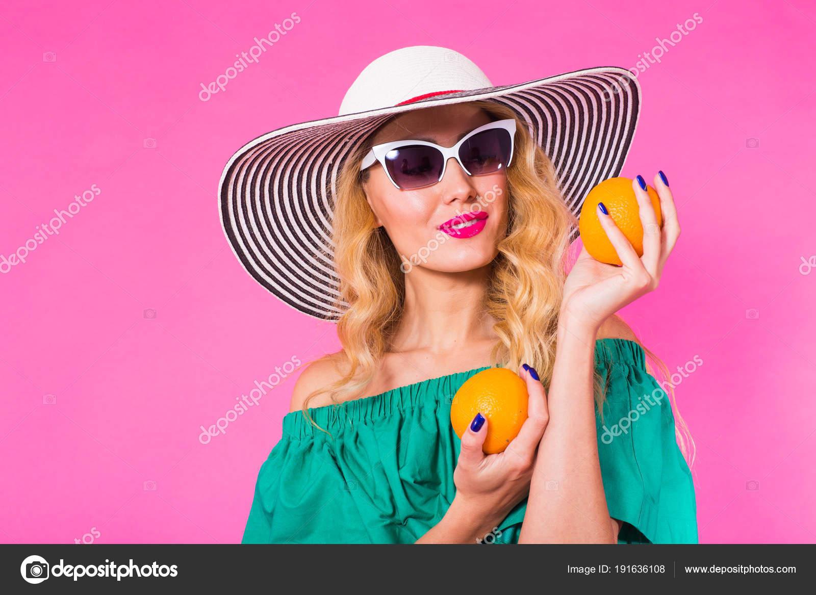 a115ae96b26ba Linda mulher elegante óculos escuros e chapéu com laranjas se divertindo  sobre fundo rosa. Verão