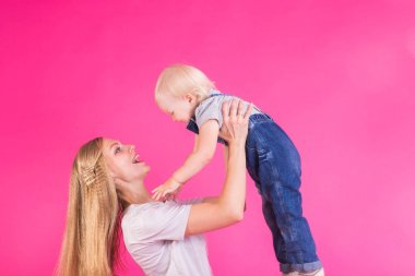 mother and daughter having fun isolated on pink background