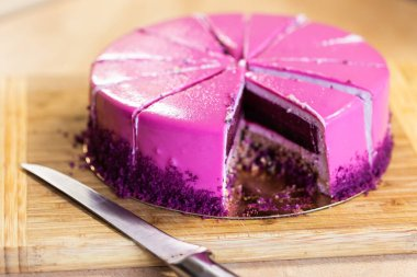 Pink and violet birthday cake without one piece. Dessert, holidays and delicious concept.