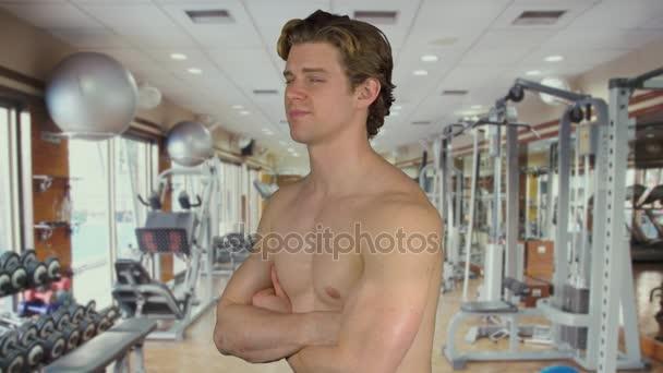 Muscolare uomo con braccia incrociate in una palestra
