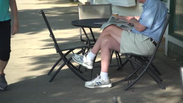 Reading a papír, a járdán, egy kávézó, az ember