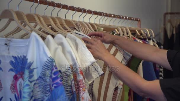 Frau durchsucht Kleidungsstücke in Bekleidungsgeschäft