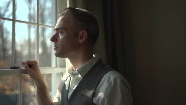člověk při pohledu z okna z tmavé místnosti