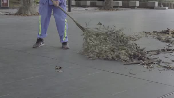 Low view of Chinese man sweeping with natural broom