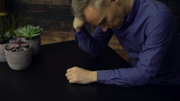 Depressed man seated at a table