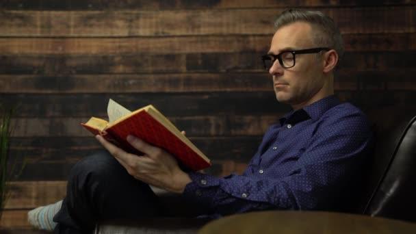 Muž v křesle čtení vázaná kniha