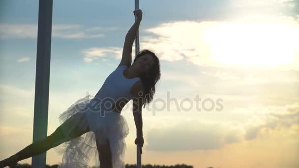 sexy attraktive Poledancerin führt fortgeschrittene Pole Dance Tricks bei Sonnenuntergang auf tragbarer Tanzbühne über der Skyline vor.