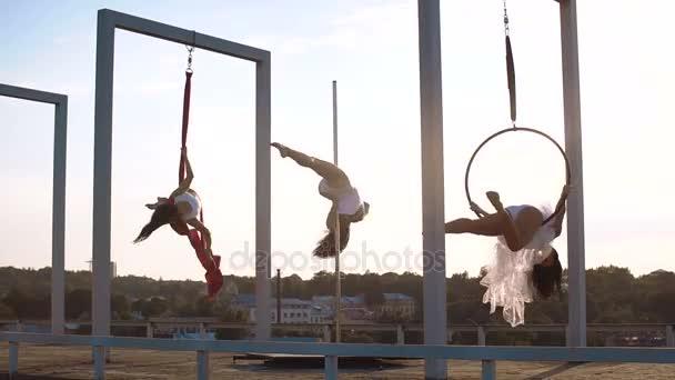 Tři krásné sexy dívka provádějící akrobatické kousky na střeše s krásným výhledem