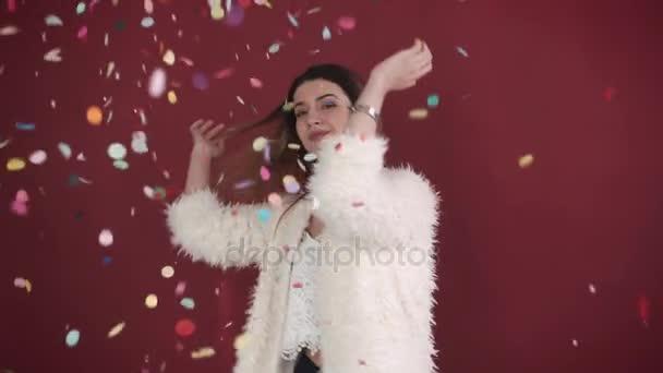 Gyönyörű lány között színes konfetti, lassú mozgás. Szexi nő táncol között konfetti piros háttér.