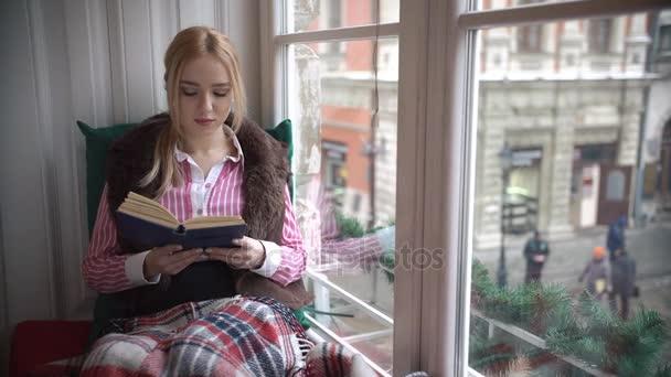 schöne junge Frau sitzt auf der Fensterbank, liest ein Buch und schaut aus dem Fenster