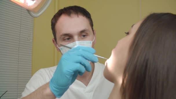 Zubař zkoumá pacientka v zubní ordinaci.