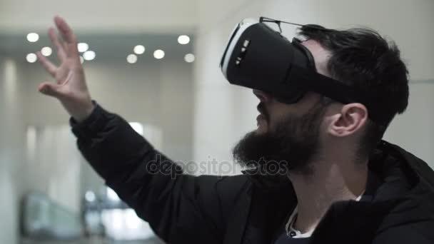 Mladý muž používající virtuální realita brýle v nákupním centru