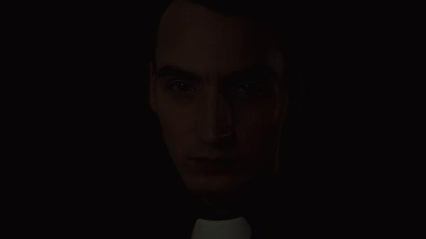 Detailní portrét kněze na černém pozadí
