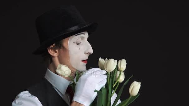 mime muž s kyticí květin na černém pozadí