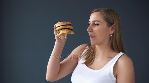 Obézní žena jíst hamburger na šedém pozadí. Koncept škodlivých potravin, nadváhy