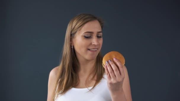 Obézní žena nemůže zvolit, co je apple nebo hamburger. Ona si vybere hamburger. Koncept škodlivé potraviny, fast food