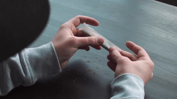 The hands of the man Twists Marijuana in Blunt - The concept Illicit Drugs, drug use, close-up