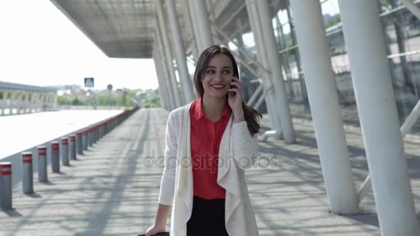 Woman in red shirt talks on the phone walking with a suitcase
