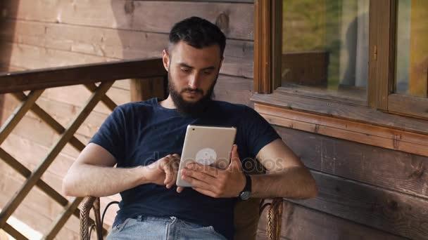 mladý vousatý muž používá tabletu, zatímco sedí na verandě venkovského domu