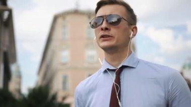 Young man talks via headphones on the street