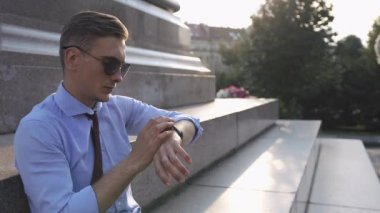 Young man works with his smartwatch